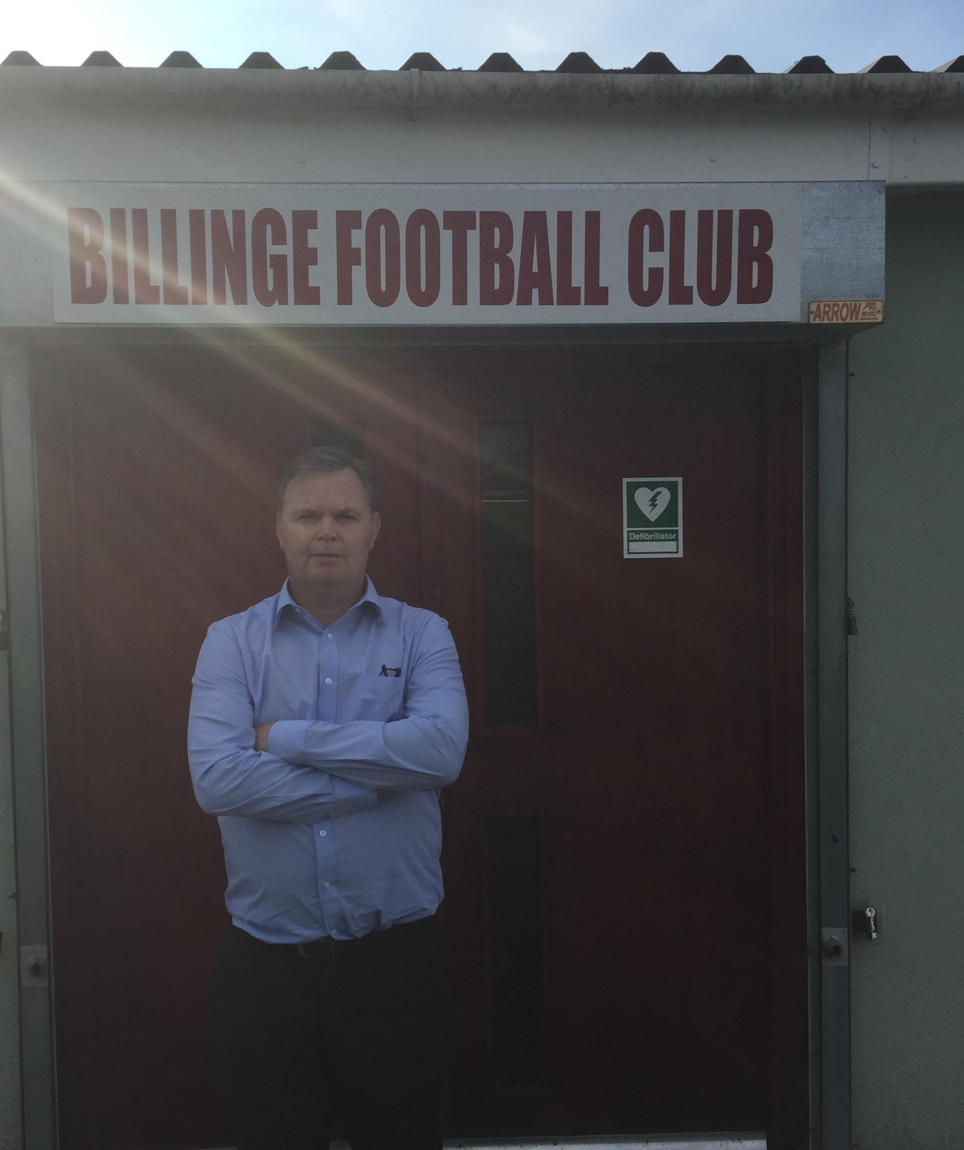 John Evans stood below Billinge Football Club sign
