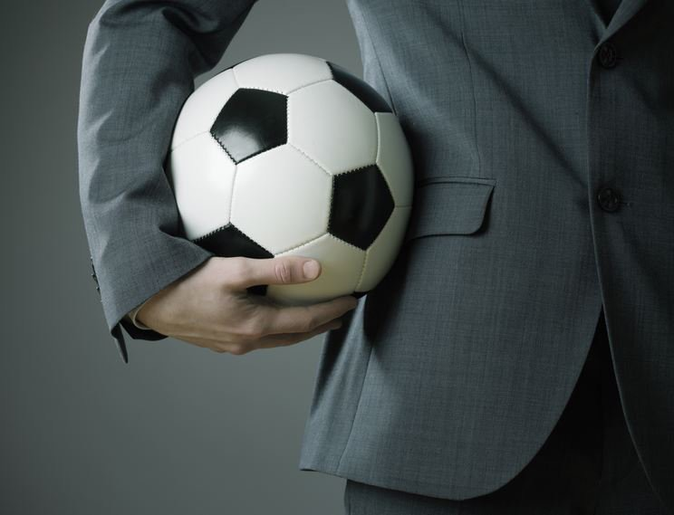 Man in suit holding football